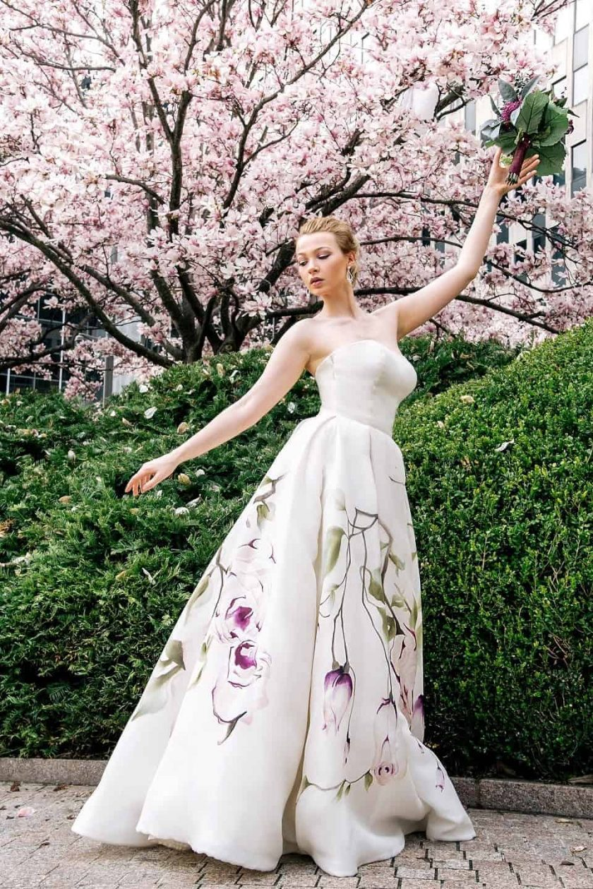 Kissing rose hand painted bridal gown with model holding her bouquet up high