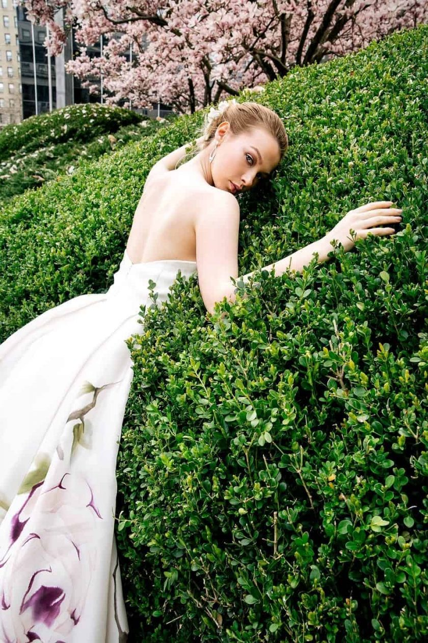Kissing rose hand painted bridal gown with bride leaning on a large boxwood bush