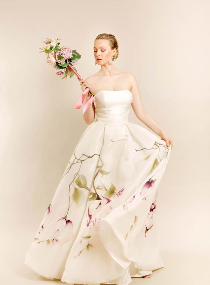 Kissing rose hand painted bridal gown with model in motion and holding bouquet up in right hand