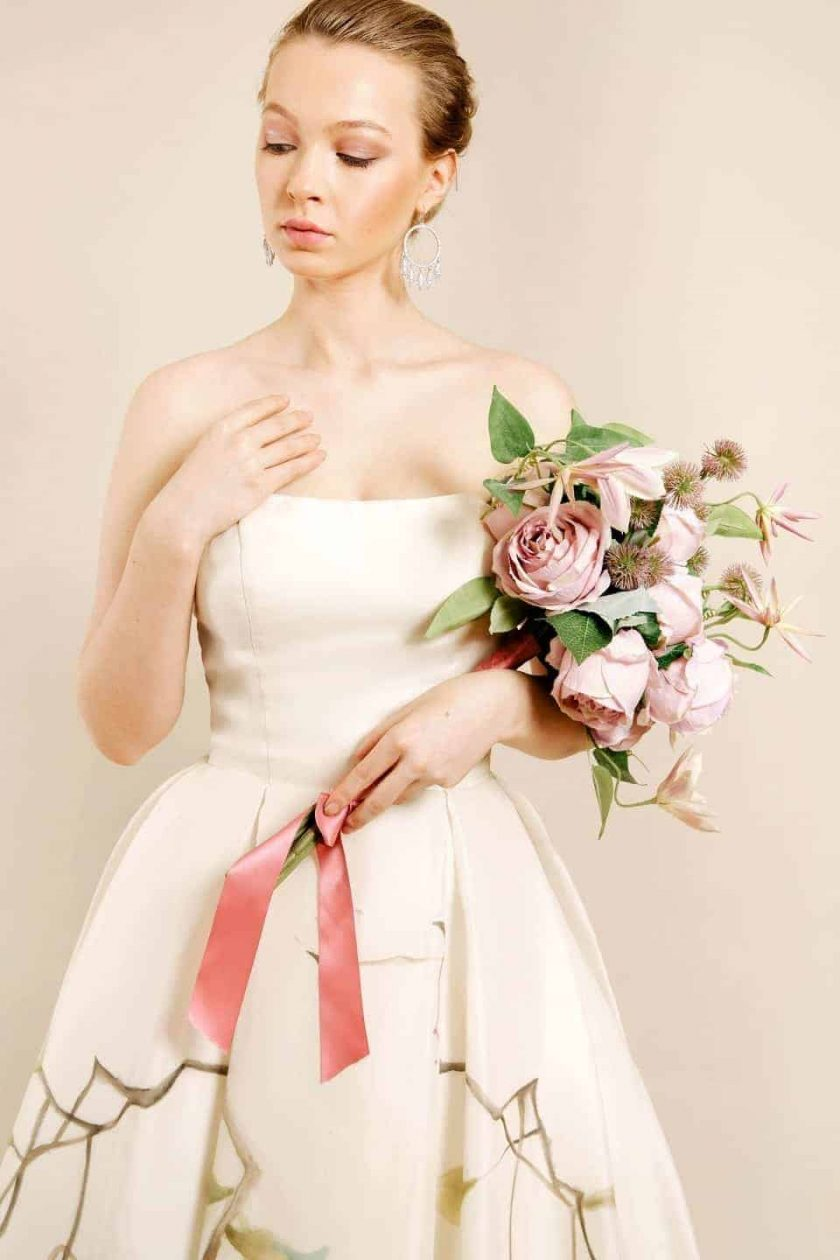 Kissing rose hand painted bridal gown model cradling a bouquet
