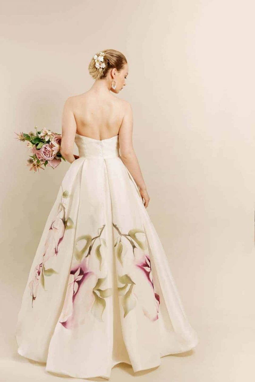 Kissing rose hand painted bridal gown rear view with bouquet in left hand