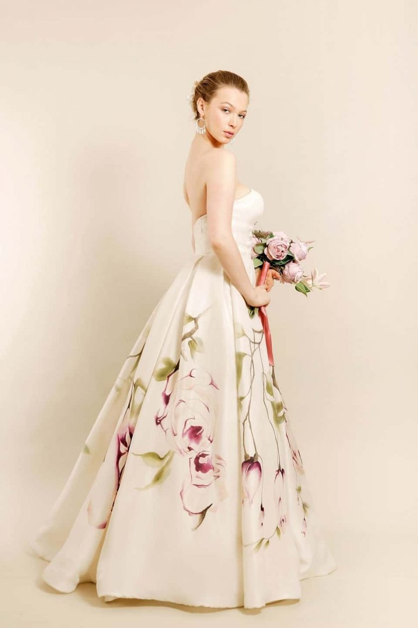 Kissing rose hand painted bridal gown side view with bouquet in hands