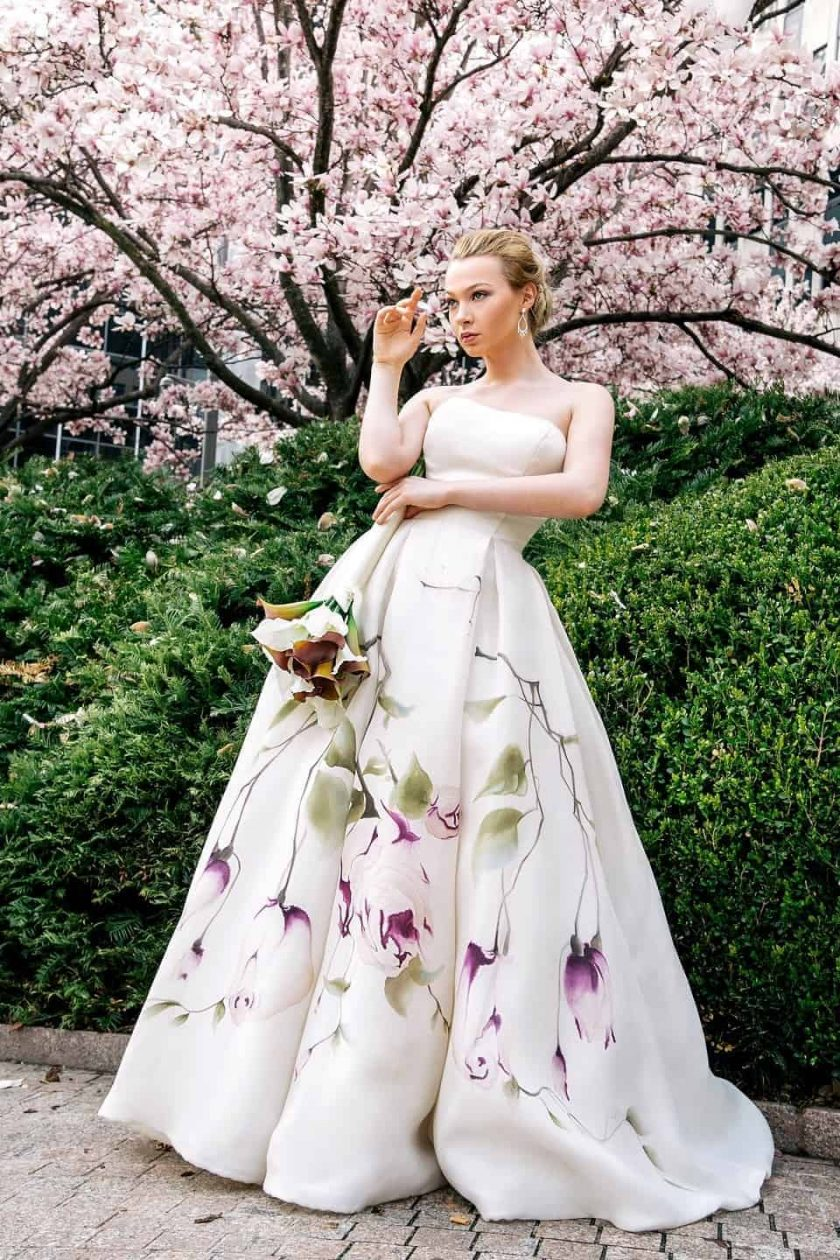 Kissing rose hand painted bridal gown with her arms folded, right hand up