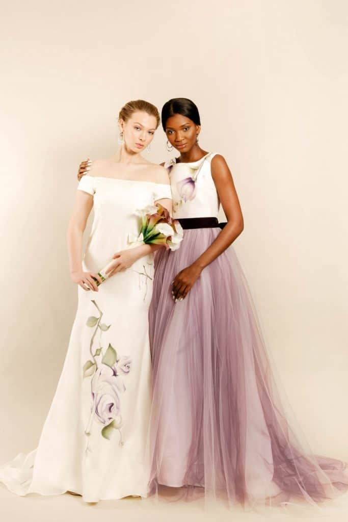 Models wearing Zahra Batool Couture Lavender Love and Vintage Rose hand painted bridal gowns facing front towards camera