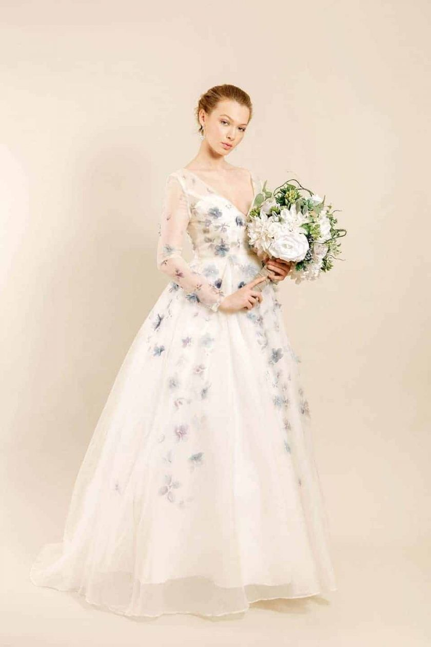 Romancing petal hand painted bridal gown three quarter front view with bouquet of white flowers with greenery