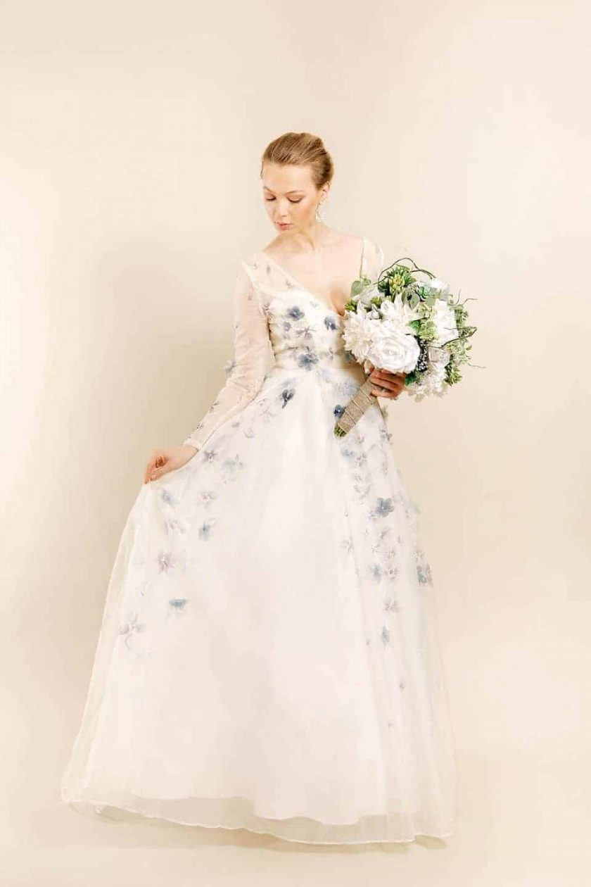 Romancing petal hand painted bridal gown with model carrying a large white bouquet