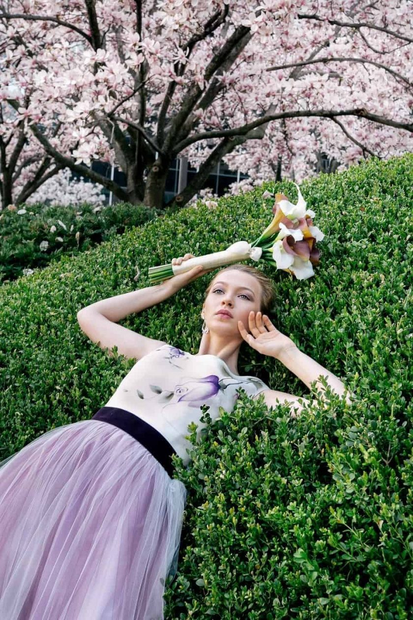 Vintage plum hand painted bridal gown worn by model who leans against boxwood bush