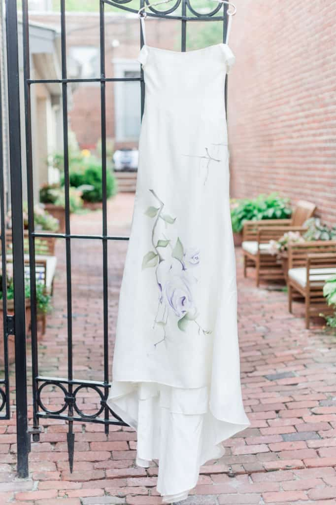 Lavender Love wedding dress hanging on the gate of the garden where the wedding took place. A custom wedding dress by bridal designer ZB Couture