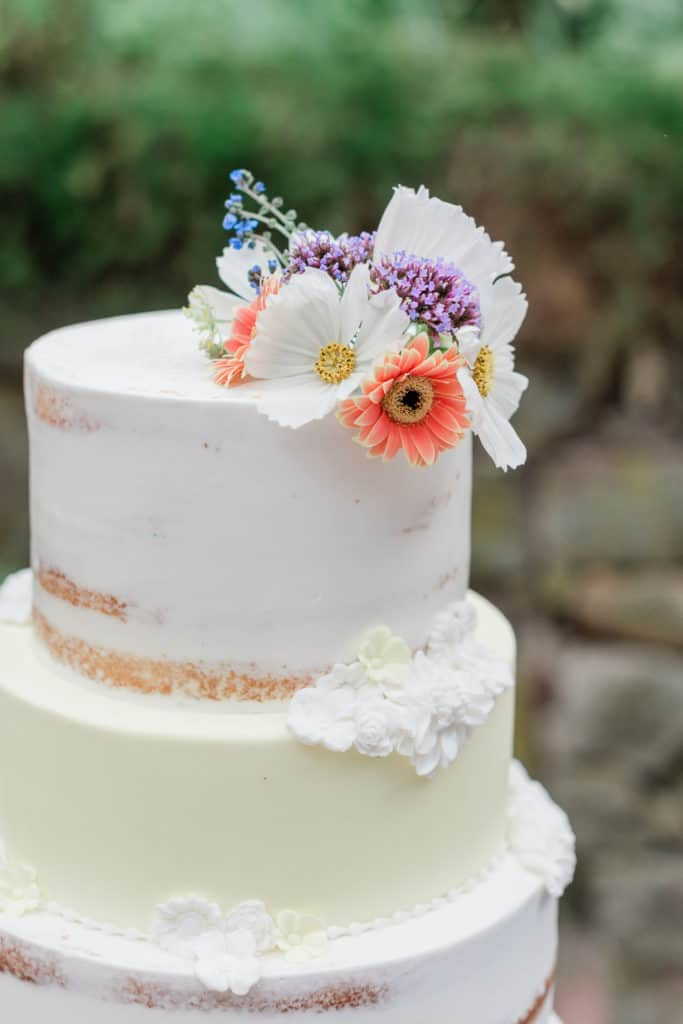 three tier wedding cake frosted in white and decorated with live flowers and frosting flowers