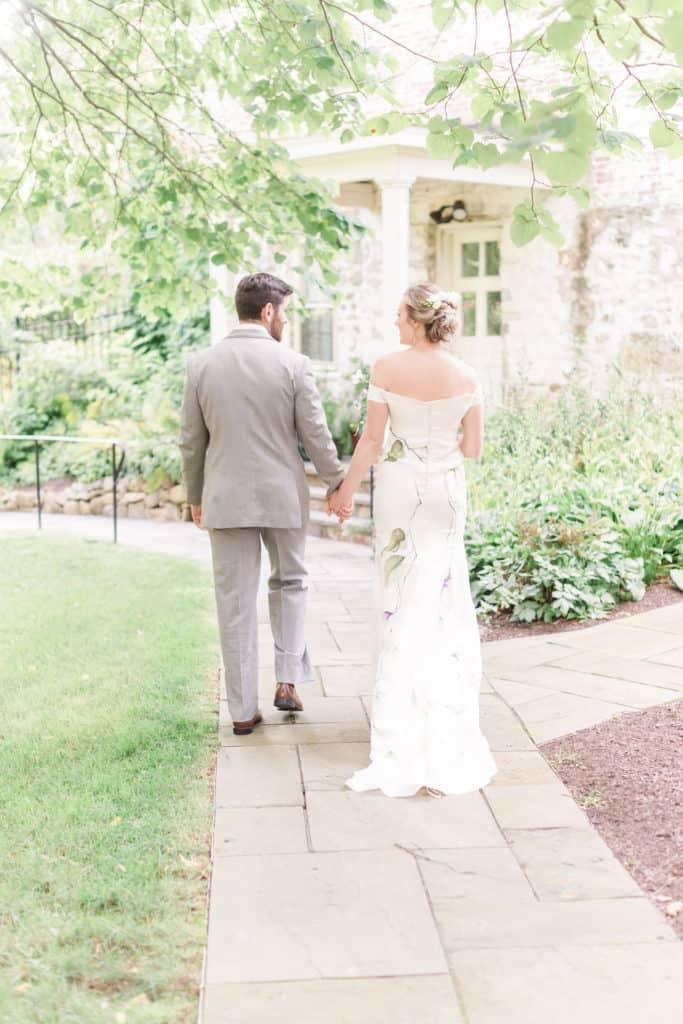 Bride and groom walking away from the wedding. Bride is wearing Lavender Love custom wedding dress