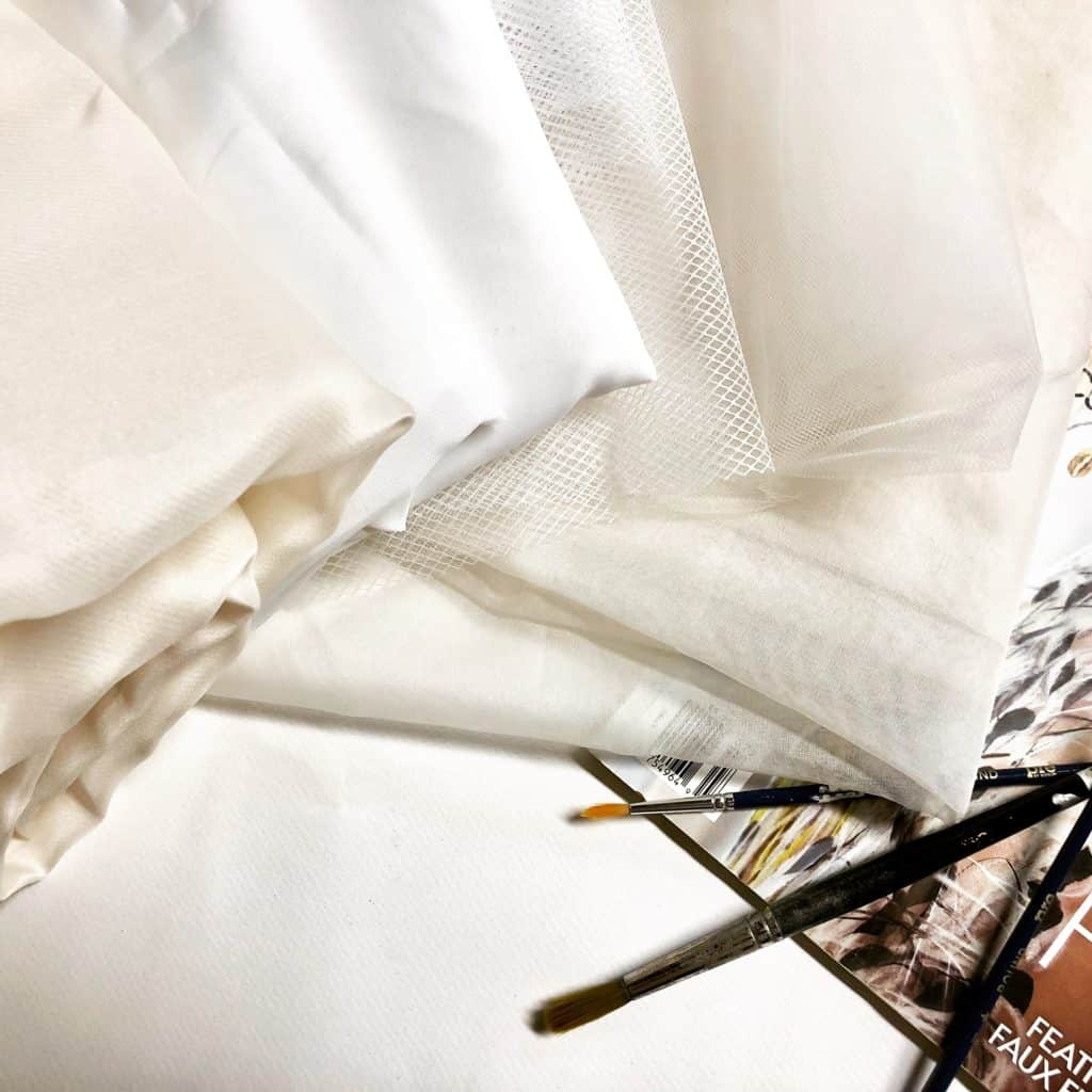 Folded Silk Fabrics on a worktable with small paintbrushes and the edge of a fashion magazine