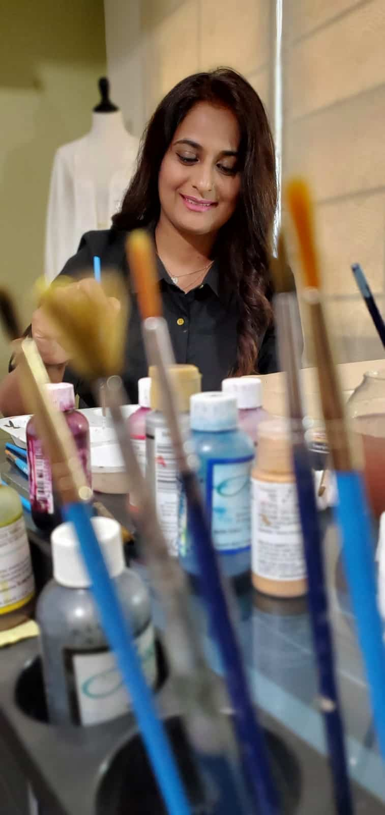 Zahra Batool of Zahra Batool Couture at work desk with paints and delicate brushes